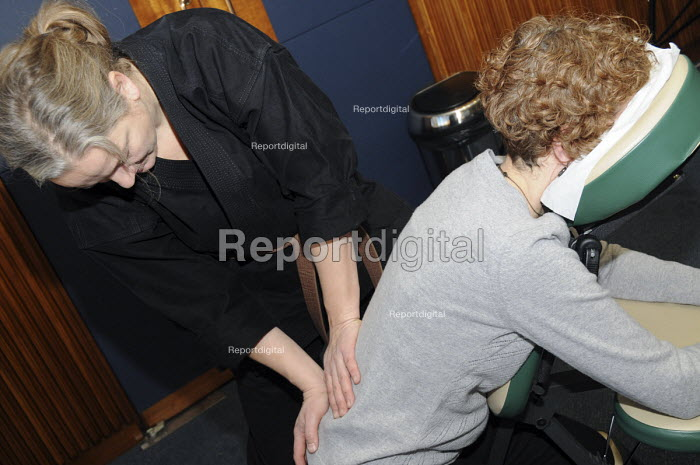 A female martial arts practitioner giving a Shiatsu neck and back massage to a women at BECTU women's trade union conference. - Janina Struk - 2008-11-22