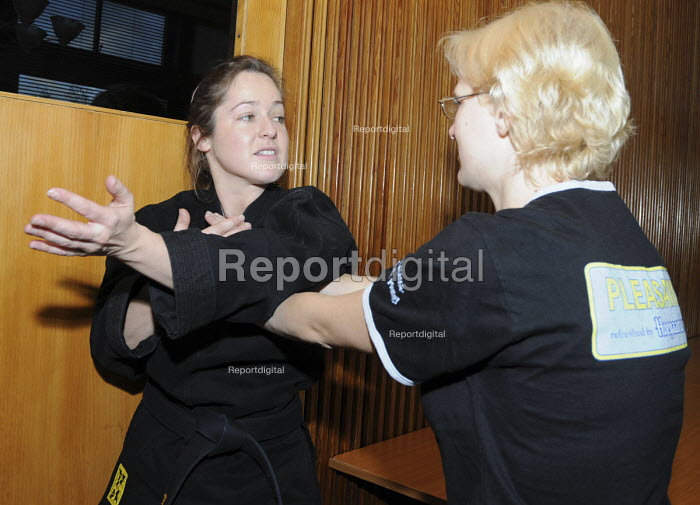 A young female martial arts instructor demonstrates a self defense technique with a woman at BECTU women's trade union conference. - Janina Struk - 2008-11-22