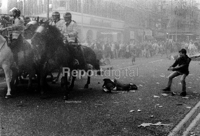 A horrified witness runs towards a demonstrator trampled under the mounted police horses during the Poll Tax demonstration on Charing Cross Road, in London. - Janina Struk - 1990-03-31