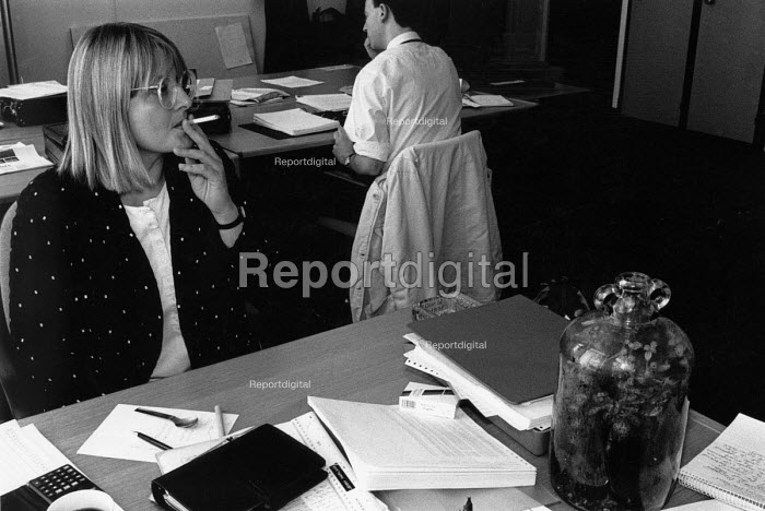 A woman smoking a cigarette at her office desk before the smoking ban was enforced. - Janina Struk - 1992-03-12