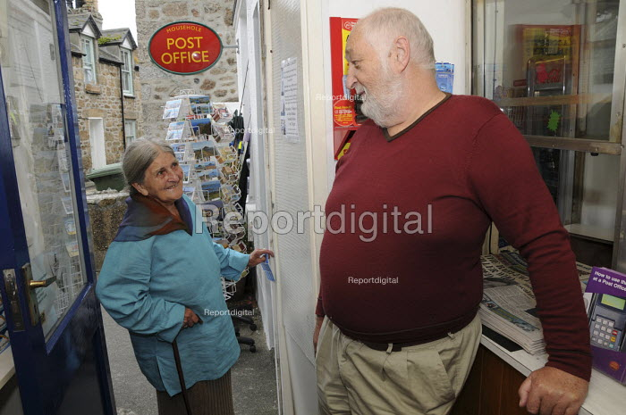 Postmaster Richard Barker who works alone at a small village post office that also sells groceries and postcards enjoys a conversation with an elderly regular customer. Cornwall - Janina Struk - 2009-09-18