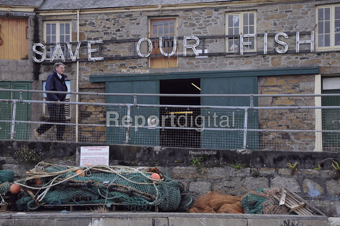 Save Our Fish sign outside a warehouse in Newlyn harbour, one of the largest remaining fishing ports in Britain. Fears of the local community as over-fishing and EU Quotas have decimated Newlyns once thriving fishing industry. - Janina Struk - 2009-09-20