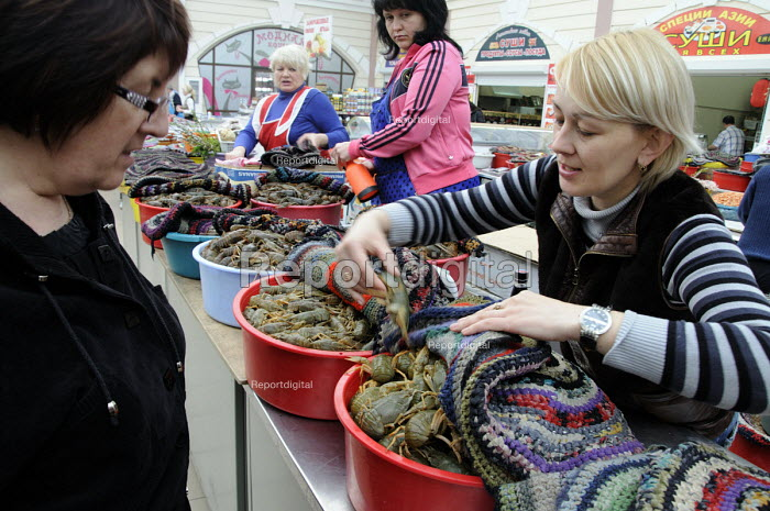 A female assistant shows a cusotmer giant live black prawns in the fish market in Odessa. - Janina Struk - 2012-03-28