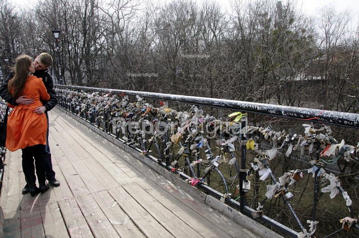 A heterosexual young couple kiss on Chortov Bridge, or The Bridge of Love, bridge in a Kiev city park where lovers lock padlocks to the bridge and throw away the key as a symbol of their love and commitment. - Janina Struk - 2012-03-24
