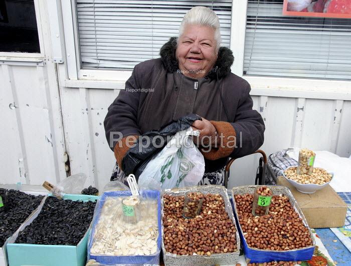 An elderly woman market trader selling nuts and sunflower seeds in a street market in Crimea, Ukraine. - Janina Struk - 2012-03-28