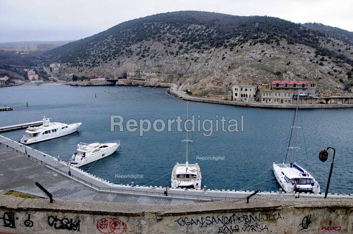 Luxury yachts in the bay and graffiti on a wall, Balaclava in Crimea, Ukraine. - Janina Struk - 2012-03-28
