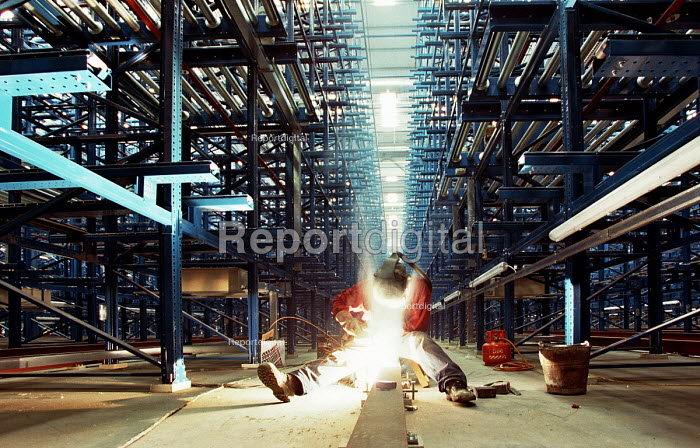 A welder working on the construction of an automated distribution warehouse - John Sturrock - 2004-04-10