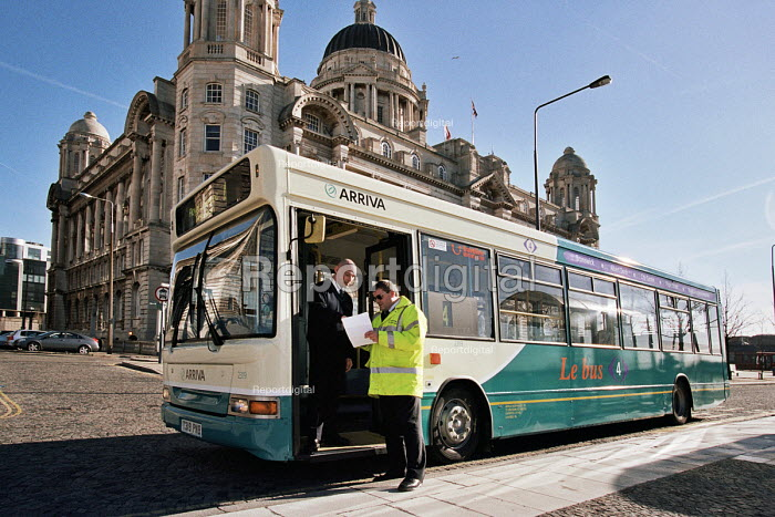Arriva bus service Liverpool. An inspector talks to a bus driver on the steps of his single decker bus - John Sturrock - 2006-03-13