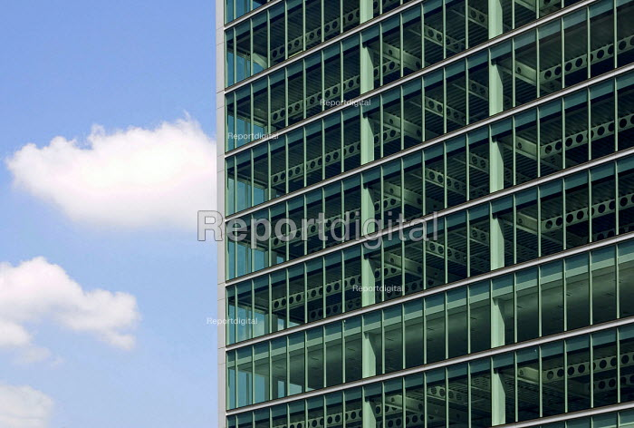 Blue sky ands whiite clouds beside the glass windows and exposed steel beams of a newly built and as yet unoccupied office block near Appold St, in Hackney on the edge of the City of London - John Sturrock - 2004-05-17