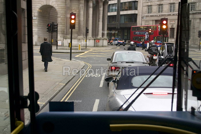 Looking through the front window of a bus at cars and a pedestrian on Moorgate while waiting at the traffic lights at the corner of Lothbury. The columns are at rear of the Bank of England - John Sturrock - 2004-06-03