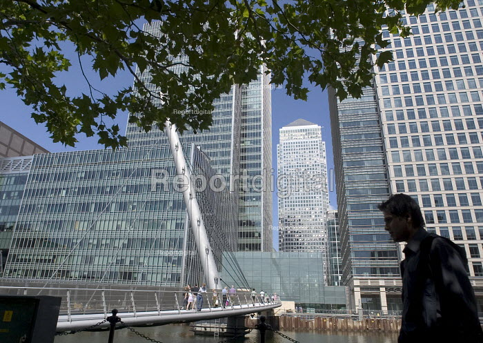 The silhouette of a man walking beneath leafy branches in front of a pedestrian bridge and bright sunlight office blocks at Canary Wharf, Docklands, London - John Sturrock - 2004-07-30