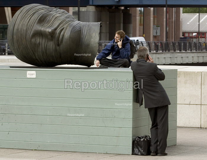 Two men using mobile phones beside the plinth of the bronze statue of a severed head wrapped in bandages, Sculpture Testa Addormentata, 1983 (bronze), by Igor Mitoraj. located on Heron Quays, beside Canary Wharf in Docklands - John Sturrock - 2004-08-26