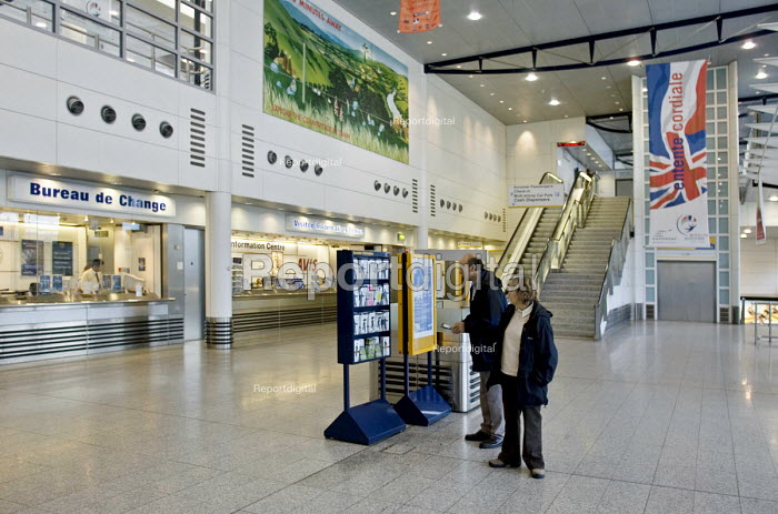 A man and woman looking at information in the empty booking hall of Ashford International Station, Kent - John Sturrock - 2004-09-14