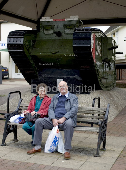 Retired man and woman visiting Ashford for a shopping trip, sitting in front of a monument that displays a First World war tank - John Sturrock - 2004-09-14