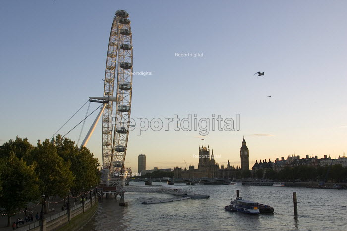 Looking west at sunset past the BA London Eye a major landmark and tourist attraction on the south bank of the River Thames towards the Palace of Westminster - John Sturrock - 2004-09-15