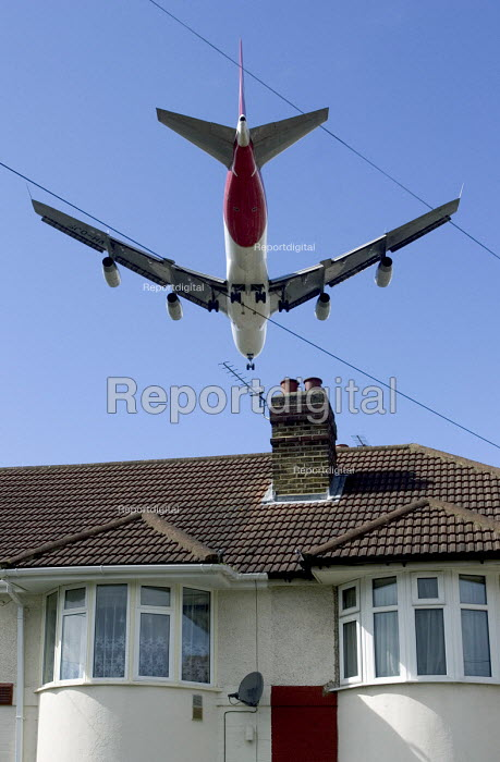 Large four engined passenger aircraft, flying low over suburban house roof, shortly before landing at Heathrow Airport London - John Sturrock - 2005-04-07