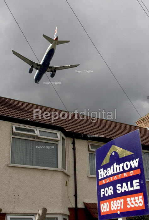 A two engined British Airways passenger aircraft, flying low over suburban house roof, shortly before landing at London Heathrow Airport. A For Sale sign is displayed outside the house - John Sturrock - 2005-04-07