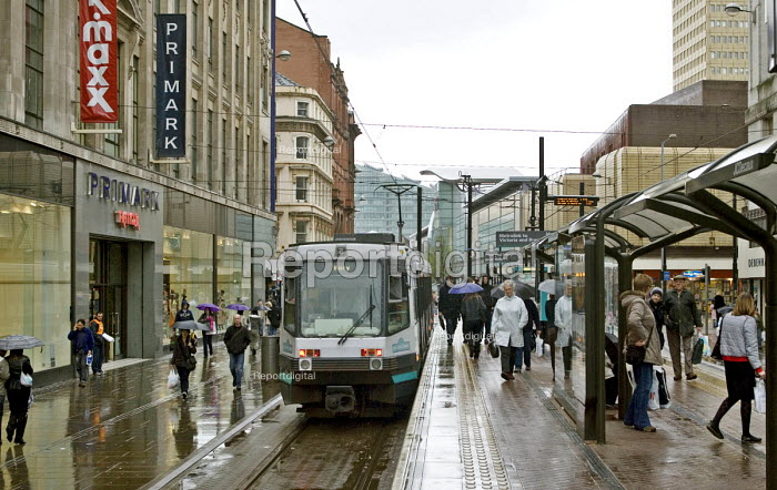 A Metronet tram departs from the platform leaving shoppers in a wet Market Street, central Manchester - John Sturrock - 2005-04-18