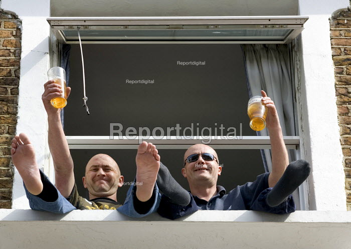 Two men, holding partially drunk pint glasses of lager, sitting and waving, with their feet out of a first floor window - John Sturrock - 2005-05-18