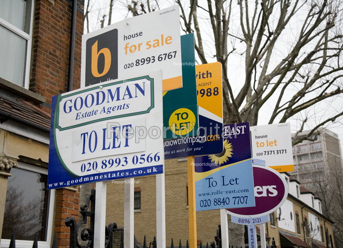 Estate Agents for sale signs outside a hard to sell detached house, surrounded by high rise housing estates in Acton, west London - John Sturrock - 2006-02-02