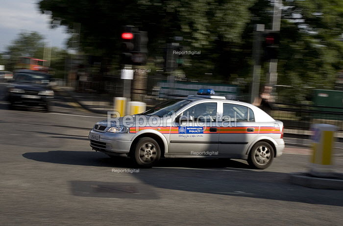 A Metropolitan police car speeding though a traffic light controlled junction in Ealing - John Sturrock - 2004-07-30
