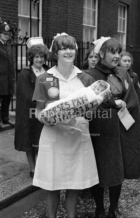 A delegation of nurses, in uniform, from the Union COHSE, outside No 10 Downing Street, during wage negotiations in London, during the winter of discontent 1979 One of the nurses holds up a doll marked with the slogan Nurses Pay - Jims Baby - John Sturrock - 1979-02-21