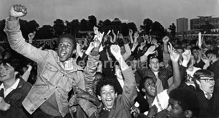 Rock Against Racism concert by The Specials, The Butts, Coventry 1981. An enthusiastic group of black and white youth cheer in the audience - John Sturrock - 1981-06-20