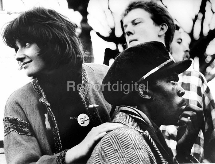 White woman wearing an Anti Nazi League badge together with a black man at the Rock Against Racism carnival in Victoria Park, Hackney, April 1978 - John Sturrock - 1978-04-30