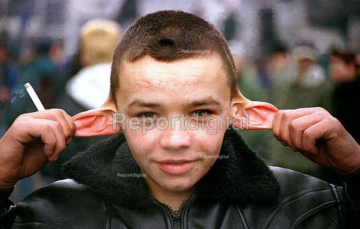 An orphan boy showing his ear trick. Belgrade, Serbia. 1996 - Andrija Ilic - 1996-07-01