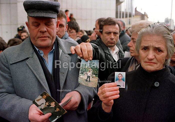 Woman holding photographs of missing relatives at demonstration by Serb families whose relatives have been kidnapped in Kosovo. Pristina, Kosovo. 1998. - Andrija Ilic - 1998-07-01