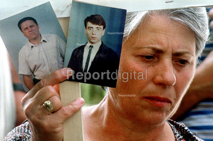 Serb woman showing pictures of her family who disappeared after NATO forces entered Kosovo in 1999. Belgrade, Serbia. 2001 - Andrija Ilic - 1998-07-01