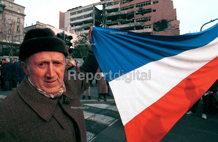 Miloshevic supporter in front of a building damaged during NATO bombing campaign. Belgrade, Serbia. 2000 - Andrija Ilic - 2000-07-01