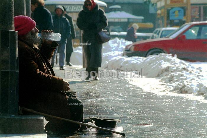 An elderly homeless man sits on the street and begs in central Belgrade. Belgrade, Serbia 2004 - Andrija Ilic - 2004-05-06