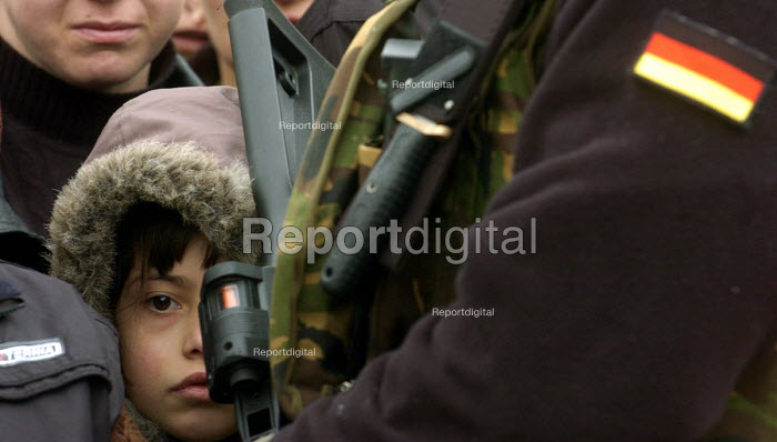 A Serb child peeks through the crowd guarded by armed United Nations police in the Serb populated village of Silovo, an isolated Serb enlclave of Kosovo.Serbian minorities are exposed daily to hostility from Kosovos Albanian extremists.2005 - Andrija Ilic - 2005-02-13