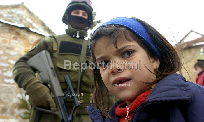 A Serb girl stands infornt of an armed KFOR soldier in the Serb-populated village of Orgaovac an isolated Serb enclave in Kosovo. Serbian minorities are exposed to daily hostility from Kosovos Albanian extremists. Kosovo 2005 - Andrija Ilic - 2005-02-21