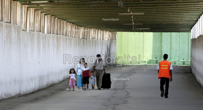 A Palestinian family walk through the security tunnel at the Erez border between Gaza Strip and Israel. Gaza 2005 - Andrija Ilic - 2005-07-06