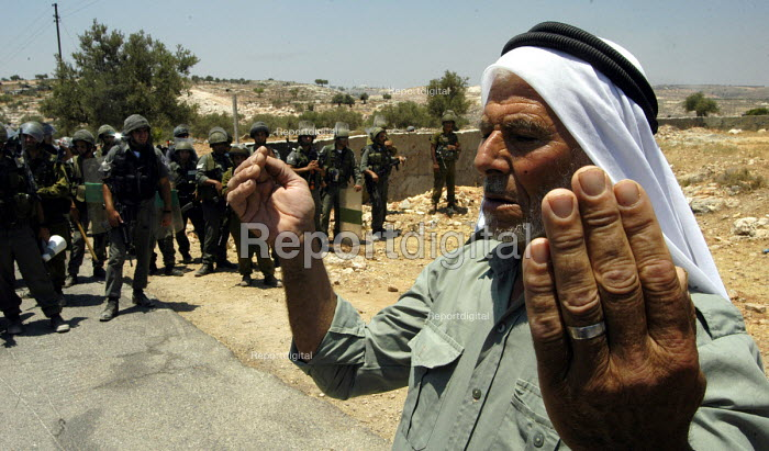 A Palestinian prays in front of Israeli troops during a joint protest with Israeli and Palestinian activists against the controversial Israeli barrier wall, village of Bilin, West Bank 2005 - Andrija Ilic - 2005-07-11