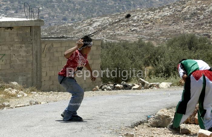 Palestinians throwing stones with slings at Israeli troops during a joint protest by Israeli, Palestinian and international peace activist against the controversial Israeli barrier wall, village of Bilin, West Bank 2005 - Andrija Ilic - 2005-07-09