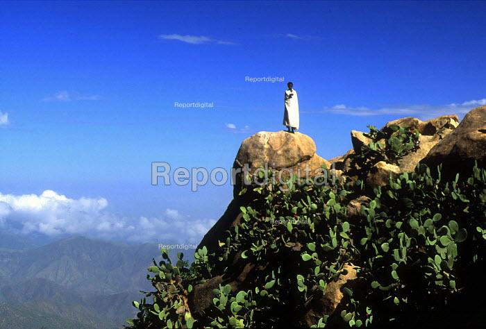 Young monk on a precipice, Mount Debre Bizen Monastery situated 2400 metres up the mountain, Eritrea 1997 - Boris Heger - 1997-09-01