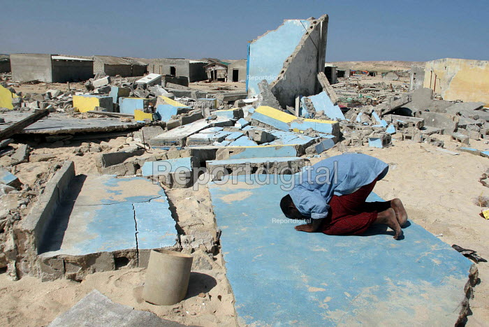 A man prays in a village damaged by the Tsunami which caused most damage in the south Asia but also reached the east African coast. Somalia 2005 - Howard Davies - 2005-09-06