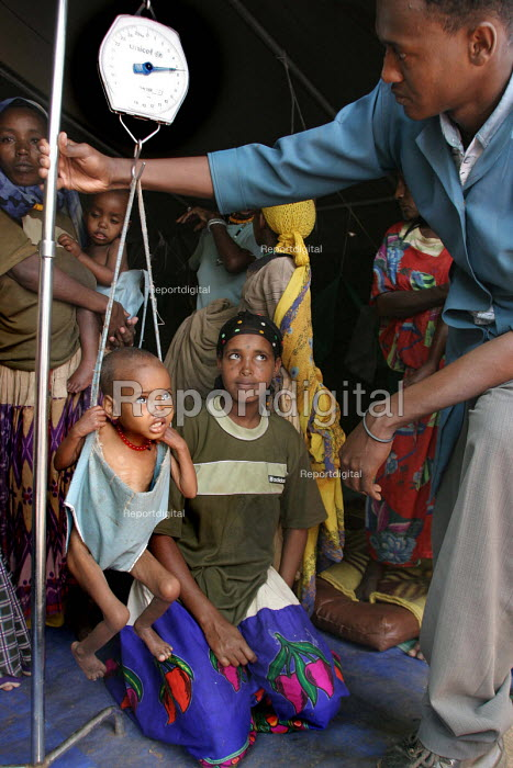 A child is weighed at a UNICEF feeding centre for malnourished children in Eastern Ethiopia. The children receive high protein supplements to assist in their recovery. Ethiopia 2005 - Boris Heger - 2005-09-06