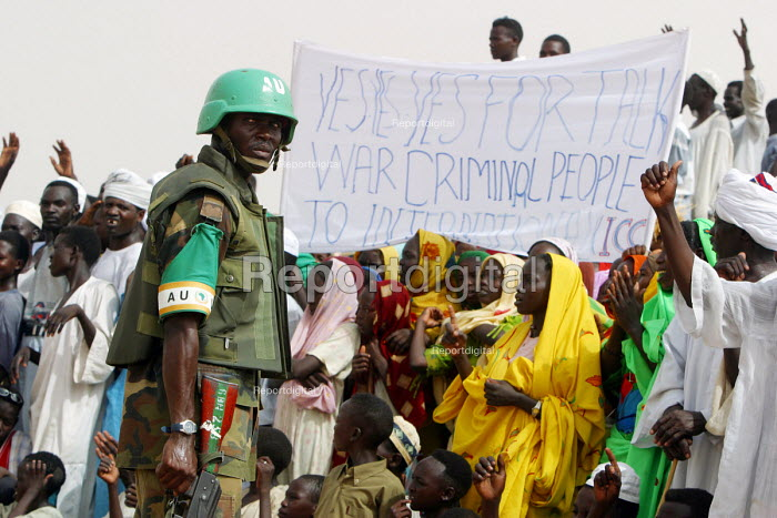 An African Union soldier watches women in a displaced persons camp, close to El Fasher demonstrate for assistance during a visit by US Government officials, Zamzam IDP camp, Darfur, Sudan 2005 - Boris Heger - 2005-06-03