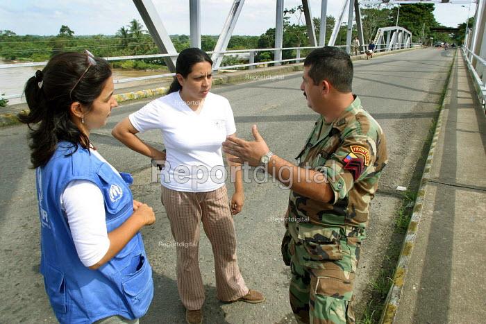 UNHCR worker with Venezuelan border guard as Colombian refugees cross the border. Amparo, Venezuela 2004 - Boris Heger - 2004-09-01