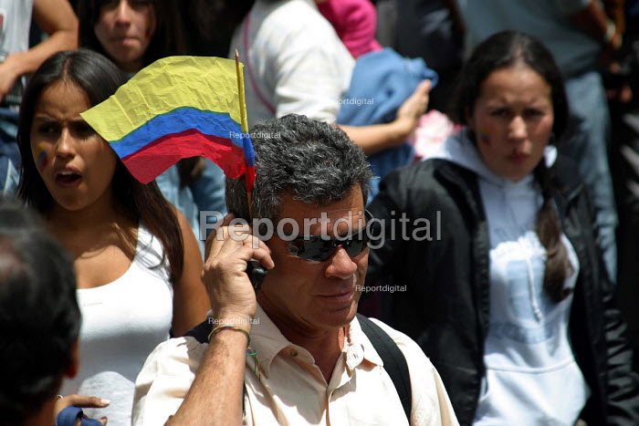 Colombian man uses his mobile phone holding a Colombian flag during a military parade in central Bogota. Bogota, Colombia 2004 - Boris Heger - 2004-09-01