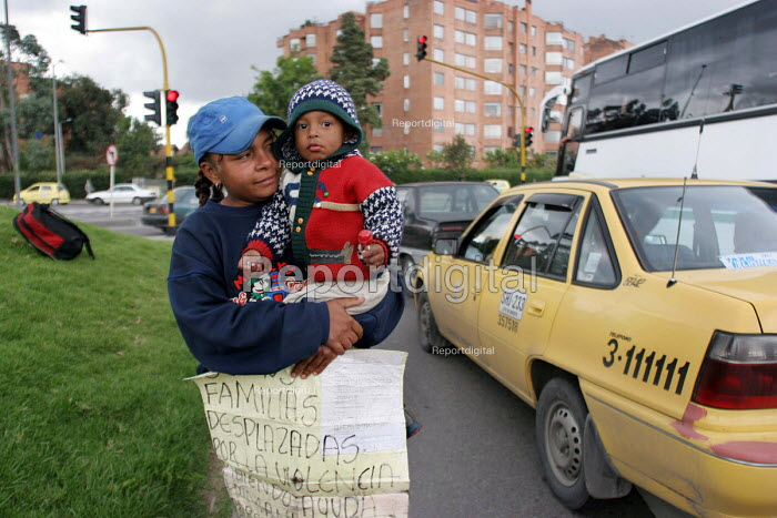 Mother begging with her child by the roadside. There are two million displaced persons in Colombia, many of whom have moved to the big cities where they live in very poor conditions in slum areas. Bogota, Colombia 2004 - Boris Heger - 2004-09-01