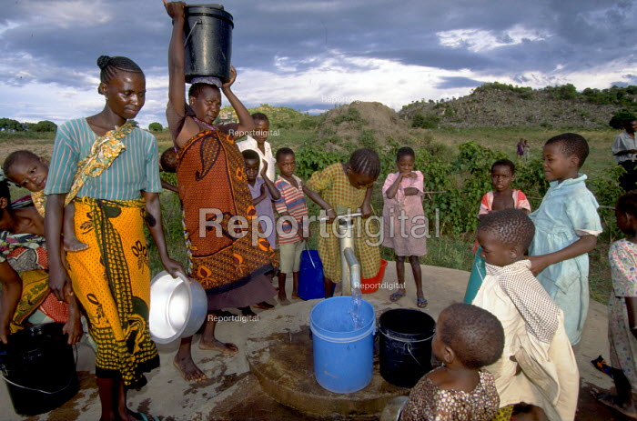 Families arriving to collect water at dusk. Uganda. - Jim Holmes - 1997-05-05