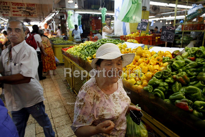 Jewish Market, Haifa, Israel. A Jewish woman, 70 years of age originally from Poland expressing her anger towards Arabs even though she buys her vegetables from a Palestinian stall owner in the jewish market and lives in the same community. - Thomas Morley - 2006-07-21