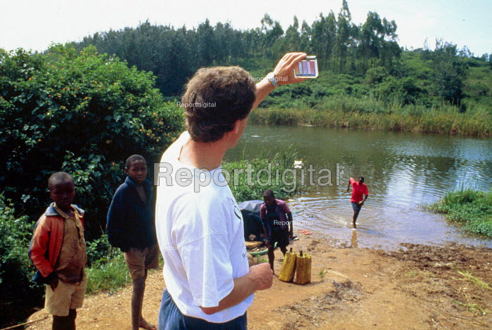 Oxfam water engineer tests water purity at a source to be used by refugees returning from Tanzania. Rwanda. 1996 The provision of clean drinking water prevents water borne disease. - Howard Davies - 1994-05-03