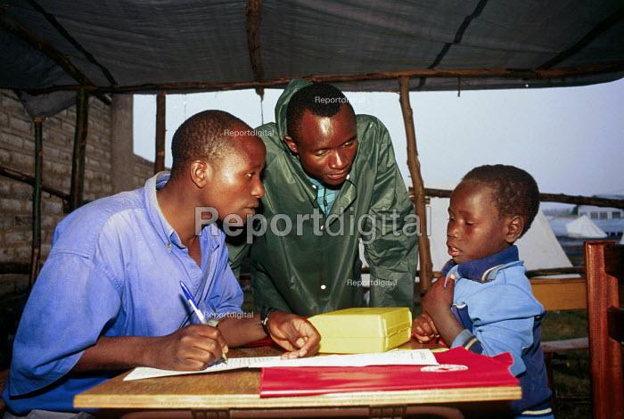 Unaccompanied Rwandan Hutu refugee child being interviewed by SCF aid workers at their Centre, Goma, Zaire. 1996 - Howard Davies - 1996-05-03