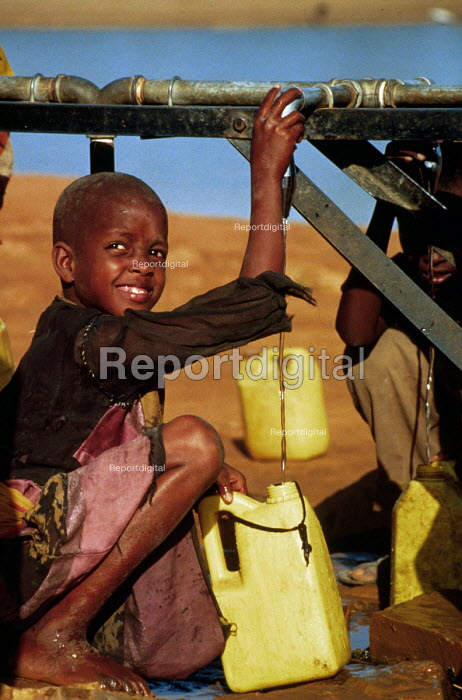 Somali children collecting clean water from an Oxfam tap stand, Bardere, Somalia. 1993 The provision of clean drinking water prevents water borne disease. - Howard Davies - 1993-05-03